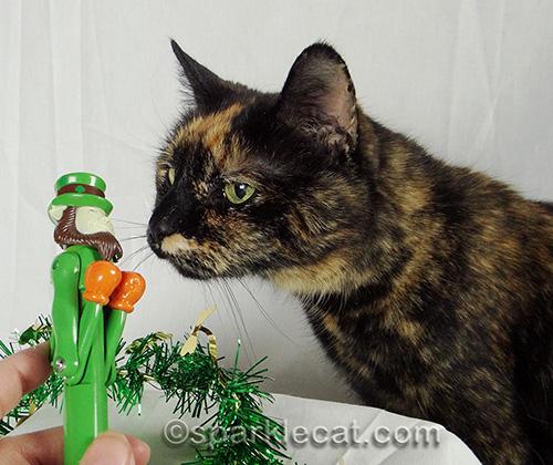 Tortoiseshell cat checking out leprechaun toy pen
